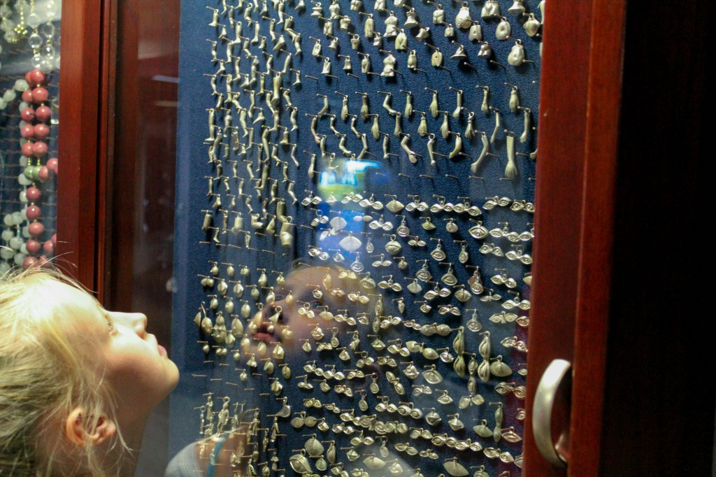 Maya is amazed at all the trinkets brought by pilgrims, the prayers and hopes of the people of Costa Rica, hanging in the glass cases at the Basílica de Nuestra Señora de los Ángeles in Cartago.